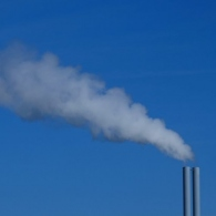 Photo of pipes releasing gas emissions into the air.