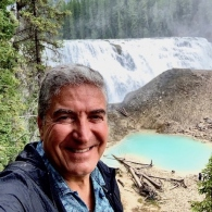 A photo of Miguel A. Romero in front of a waterfall.